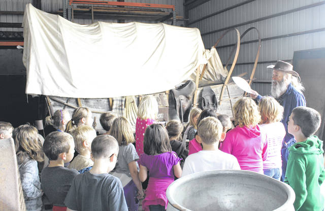 Gary Hochenberger explains the Conestoga wagon to second-graders during their annual visit with the Greenfield Historical Society. School programs like this are made possible through fundraisers like the society's annual History Day.