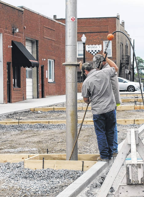"Hillsboro city workers are shown pouring concrete for a street light this week at the future ""green space"" on Governor Trimble Place."