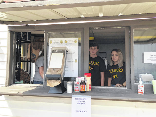 Hillsboro FFA members Logan Helterbrand and Gracie Isaacs are shown working and enjoying their time in the food booth at the fair.
