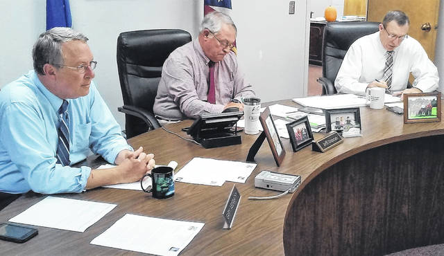 From left, commissioners Gary Abernathy, Jeff Duncan and Terry Britton go over business items at their weekly meeting on Wednesday.