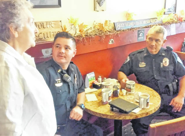 Bootsy Bursk, left shares coffee and conversation with officers Shawn Kelley and Tim Bell of the Hillsboro Police Department during Wednesday morning's Coffee with a Cop event at Momma's West Main Cafe.