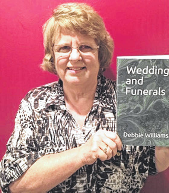 "Deb Williams holds a copy of her latest book ""Weddings and Funerals."""