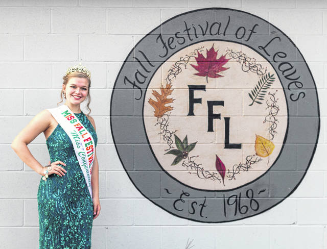 Outgoing Miss Fall Festival of Leaves Gloria Peters stands next to the FFL logo.