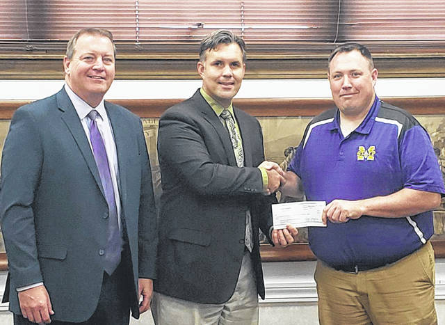 Greenfield City Manager Todd Wilkin met with local school officials recently to present a $500 check to McClain High School in recognition of the assistance provided by local students in May. MHS students collected 556 old tires to be recycled as part of their McClain Service Day activities. Pictured are, from left, are Greenfield Superintendent Joe Wills, Wilkin and McClain High School Principal Jason Potts.