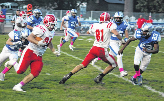 Hillsboro's Josh Keets (24) runs the ball against the Washington Blue Lions while fellow Indian Luke Middleton (81) blocks for him on Friday at Gardner Park in Washington Court House where Hillsboro took on Washington in FAC football action.