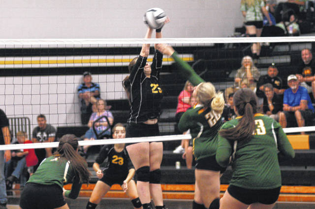 Lynchburg-Clay's Brook Laymon attempts a block in the second set of the Lady Mustangs match against North Adams at Lynchburg-Clay High School on Tuesday.