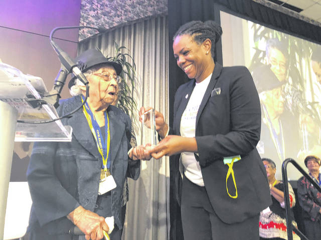 Else Young, left, 102 years old, accepts an Ohio Women Making a Difference Award on Saturday in Cincinnati on behalf of the Marching Mothers of Hillsboro.