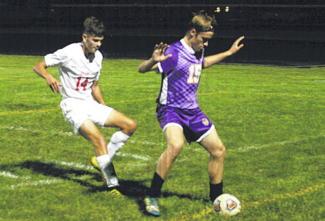 McClain's Reece Schluep attempts to block Hillsboro's Ethan Snapp from getting the ball along the sideline on Thursday at McClain High School where the Tigers took on the Indians FAC boys soccer action.