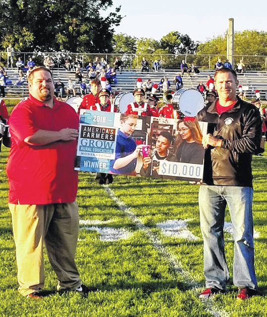 Hillsboro High School received a $10,000 grant from Monsanto at last Friday's football game. The school nominated by Kevin Surber, a local farmer, to receive the grant. Pictured are T.J. Crowder, a Hillsboro teacher who helped write the grant and Tim Davis, superintendent.