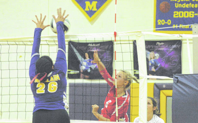 McClain senior Makenzie Montavon blocks Hillsboro's Paige Loudin at the net Thursday at McClain High School where the Lady Tigers took on cross county rivals the Hillsboro Lady Indians in FAC volleyball action.