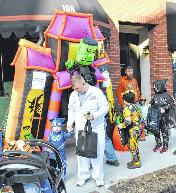 In the top photo, area youngsters are shown entering and exiting the annual haunted house held in The Times-Gazette offices Thursday on Beggar's Night in Highland County. Best Buy Motors, the Highland County YMCA and Times-Gazette staff members handed out candy, Lowe's and Walmart donated props, and the Hillsboro Uptown Business Association and the newspaper's staff did the decorating. In the bottom photo, 9-year-old Elizabeth Ogden, left, and 8-year-old Jennie Lynn, both Bright Local students, are pictured at Boo-Fest sponsored by WSRW on the Highland County Courthouse square.