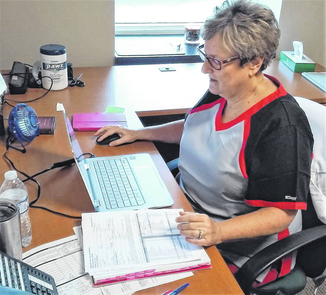 The new director of nursing at the Highland County Health Department, Debbie Iles, schedules a flu vaccinnation appointment.