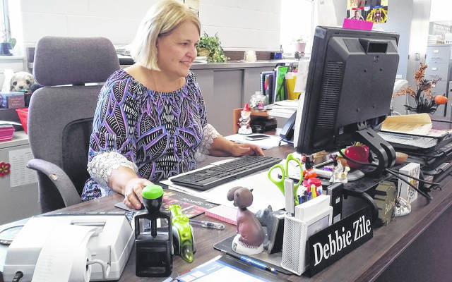Debbie Zile is shown at her desk at the Highland County Auditor's Office.