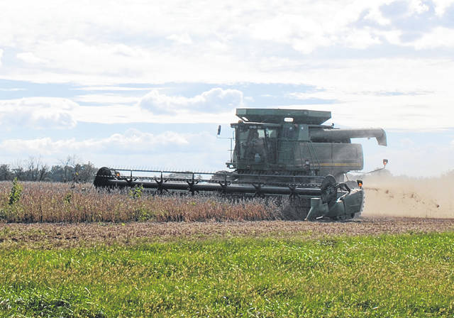 A combine spits out chaff Tuesday afternoon as it harvests soybeans at a farm on SR 72 south of Highland.