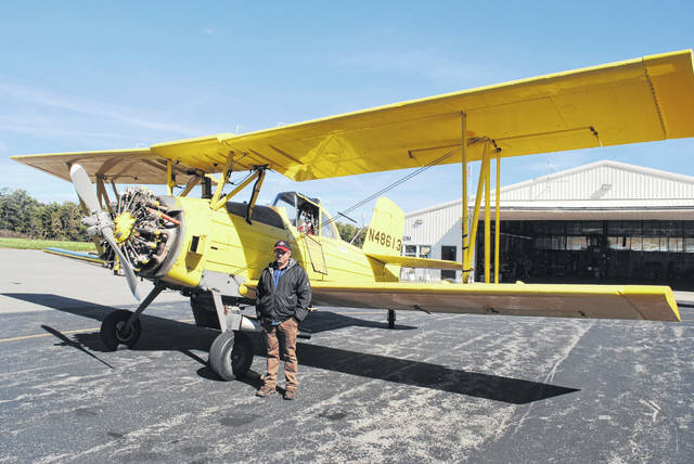 Adrian Runck of Berrysville is shown with his 1976 Grumman Ag Cat crop duster on Friday at the Highland County Airport.