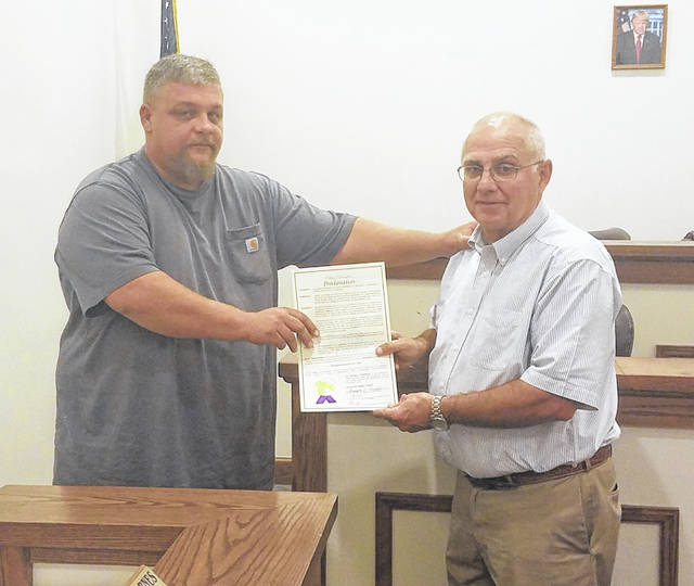 """Greenfield Village Councilman Chris Borreson presents a proclamation to Mike Penn of Greenfield Research, naming Nov. 2, 2018 """"Greenfield Research Inc. Day"""" in honor of the company, which is celebrating its 50th year."""