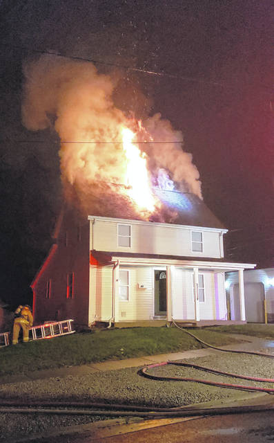 Flames are seen bursting through the top of this North East Street home after 3 a.m. Saturday. Firefighters fought the blaze for 25 minutes and kept the fire contained to the attic. There were no reported injuries.