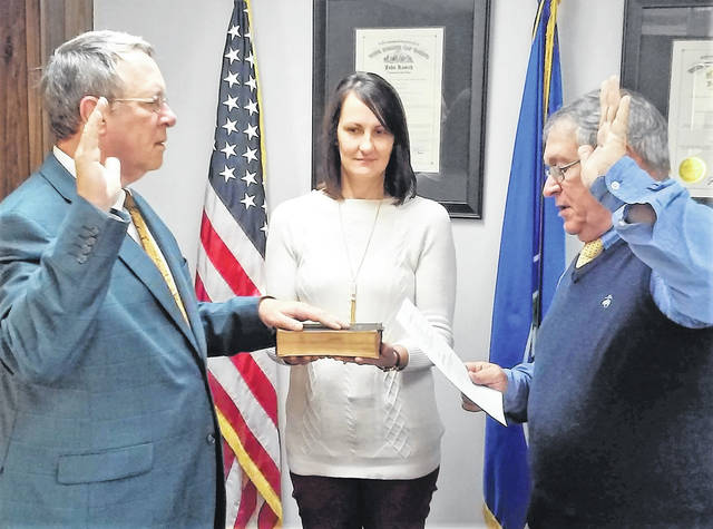 Gary Abernathy, left, elected to the Highland County Board of Commissioners earlier this month after being appointed to the position last summer when former commissioner Shane Wilkin resigned to accept a position as a state representative, took the oath of office during Wednesday morning's regularly scheduled meeting. Holding the family Bible that belonged to Abernathy's grandfather, Glenn Abernathy, is clerk Mary Remsing, middle, while Commissioner Jeff Duncan, right, is shown administering the oath.