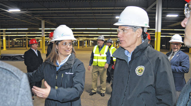 In the left foreground, Amazon Air Director Sarah Rhoads tells U.S. Sen. Rob Portman (R-Ohio) about plans for Building F, a large facility that's previously been utilized for an air freight sorting operation at the Wilmington Air Park.