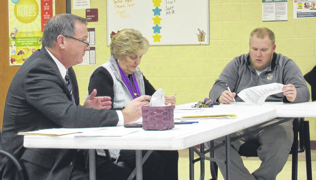 Superintendent Joe Wills, far left, gives his report to school board members at Tuesday's meeting. Also pictured are board members Sandy Free and Charley Roman.