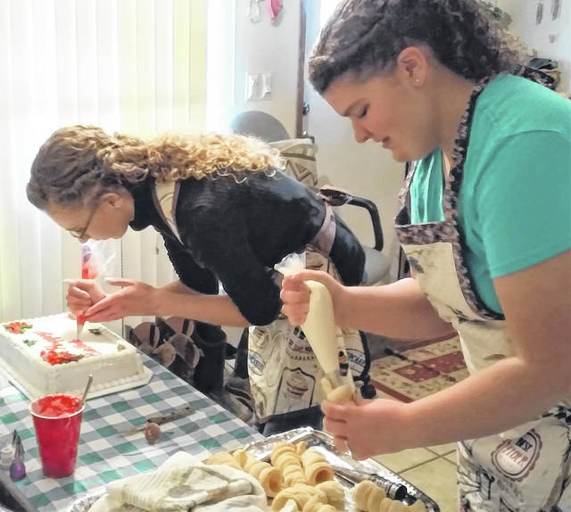 At the Rose Factory bake shop sisters Hannah and Savannah Warnock work creating baked goods for the Nov. 16 grand re-opening.