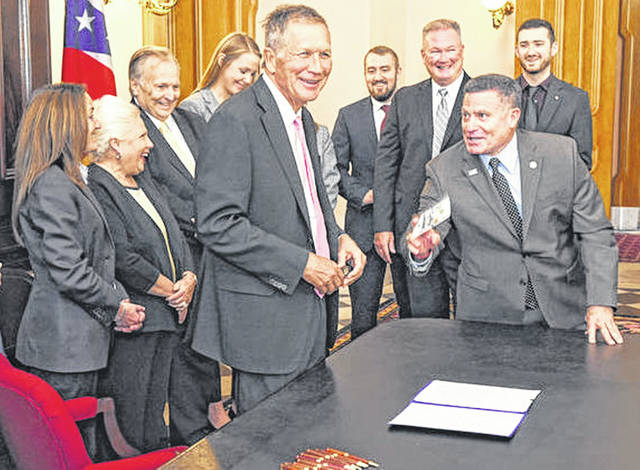 Gov. John Kasich laughs after examining a fake $100 bill brought to him by state Rep. Rick Perales before signing a law cracking down on counterfeiting.