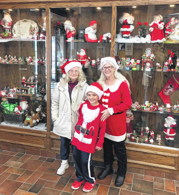 Mary Mick and her family are pictured with a display of miniature Santas currently on display at the Greenfield Branch Library. The display is in honor of Mary's husband, Jim Mick, who collected the miniature Santas.