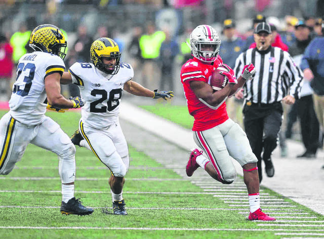 Michigan's Tyree Kinnel (23) and Brandon Watson (28) pursue Ohio State's K.J. Hill during Saturday's game at Ohio Stadium in Columbus.