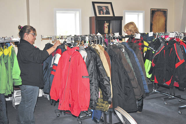 Hilda Hamilton, left, and Gayla Jones sort through coats at New Life Church and Ministries that will be given away Saturday, Dec. 1 as part of the ninth annual Storm's Christmas Blessing.