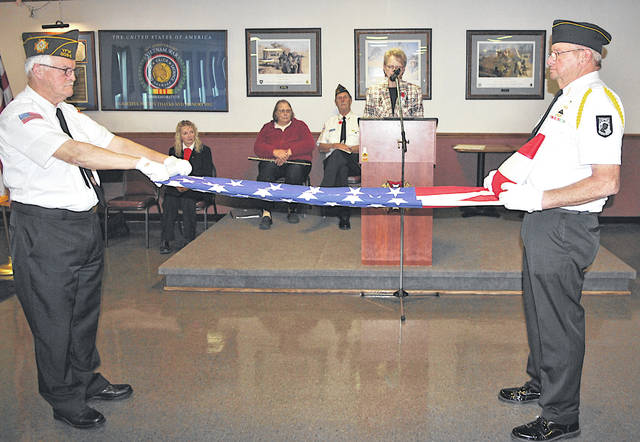 Dave Pinney, left, and John Walker display the proper way to fold a flag as Judy McCray, in the background at the podium, explains the meaning of the 13 folds.