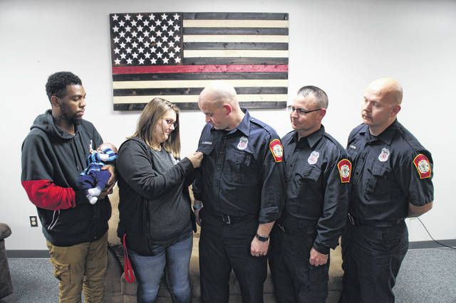 From left, Blayne Clark holds his newborn son, Jaxtyn, as his wife, Kayla Clark, pins a stork pin on Paint Creek Joint EMS/Fire District Firefighter/Paramedic Mike Sowards. Also shown are firefighter/EMTs Steve Vance and Michael Glenn. The three EMS workers helped Kayla Clark deliver Jaxtyn in the back of an ambulance on the way to the hospital.