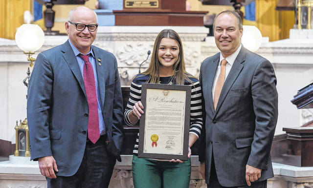 Senators Bob Peterson, far right, and Frank Hoagland, far left, are shown presenting Allison Davis of Carrollton a Senate resolution for her Ohio State Fair Grand Champion Meat Chickens.