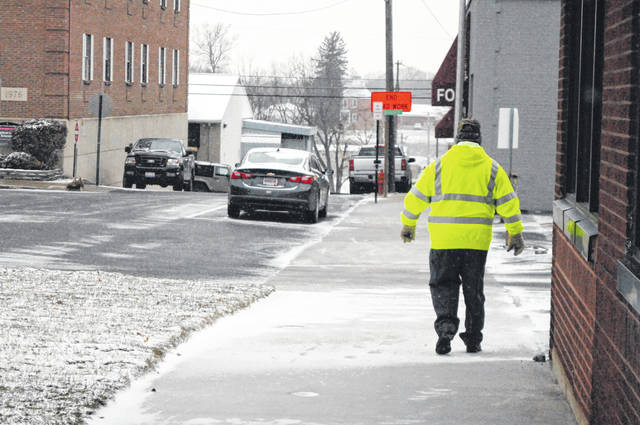 Frozen rain and snow on roadways and sidewalks made for slick travel conditions Tuesday. Shown is a pedestrian on Governor Trimble Place in Hillsboro.