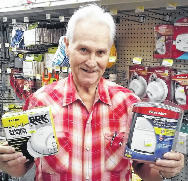 At Town and Country in Hillsboro, Larry Hunter holds two types of smoke alarms sold there. On the left is an ionization type and on the right is a combination smoke and carbon monoxide photoelectric alarm.