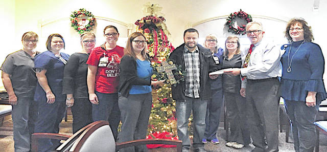 Caregivers at Adena Family Medicine-Greenfield celebrated the holiday season by holding a wreath decorating contest with patients and visitors voting on their favorites. Each of the wreaths were then raffled off with all the proceeds from the ticket sales donated to the Greenfield Area Christian Center Food Pantry. Pictured are Adena Family Medicine provider Dr. Richard Mizer surrounded by Adena Family Medicine-Greenfield staff, presenting Mike Anderson with the Greenfield Area Christian Center, with a wreath and a $200 donation.