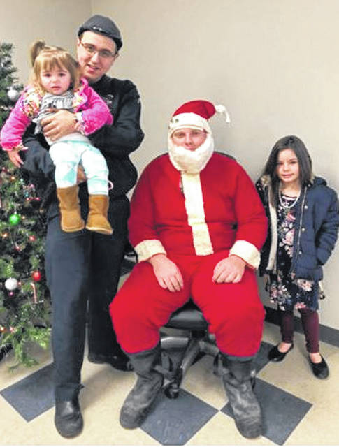 The AFSCME Local 1091, the Paint Creek Joint EMS/Fire District part-time firefighters' union, hosted its inaugural Breakfast with Santa on Saturday, Dec 8. Pictured, from left, at the event are full-time firefighter Robbie Miller holding Kyndell, part-time firefighter Spencer Boone, and Molly Vance.