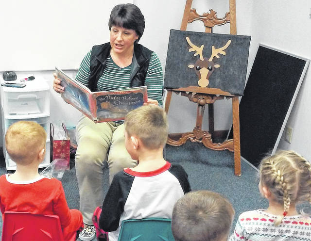 """Highland County District Library librarian and storyteller Brenda Putnam reads """"'Twas the Night Before Christmas"""" to a group of children during storytime at the library's Leesburg branch."""