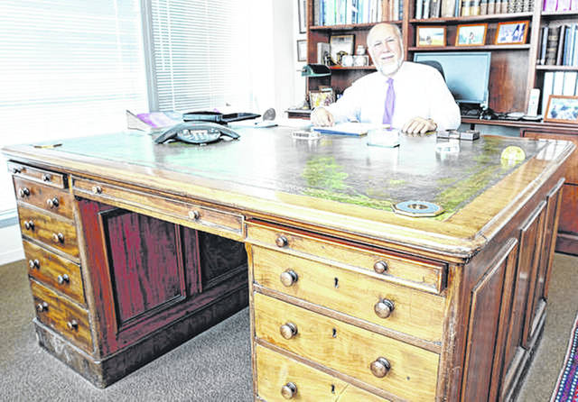 Daniel Buckley, a recently retired legal counselor and former adjunct faculty member in constitutional law at Wilmington Colleger, sits at his father's desk.