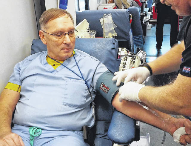 Highland District Hospital Pathologist Assistant Dave Long of Bainbridge is shown donating blood Tuesday afternoon at the HDH and Hoxworth blood drive, which will now appear here monthly, according to Lab Manager Twila Kendricks. Kendricks said the Hoxworth Bloodmobile will be stationed at the hospital on the second Tuesday of every month to take blood donations from locals. Hoxworth Assistant Field Manager Jeff Welch of Bethel is shown assisting Long.