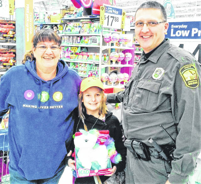 Sara Owens of Fayetteville was just one of the nearly 60 children who got to shop for Christmas gifts with an area law enforcement officer during the annual Shop With a Cop event Wednesday at the Hillsboro Walmart. Pictured, from left, are Debbie Cox, a chaperone from Clermont-Mercy Hospital near Mt. Orab; Sara Owens; and Ohio Department of Natural Resources Officer Matthew Hunt of Xenia.