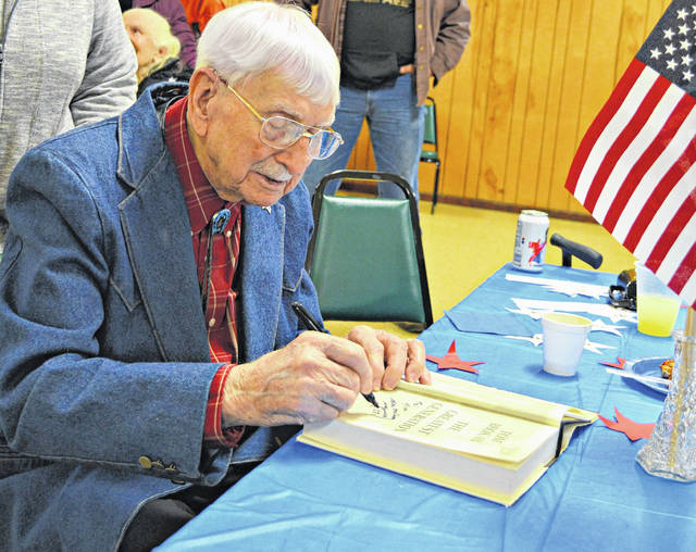 "At an open house held Saturday at the Highland County Senior Citizens Center in Hillsboro, a large crowd was in attendance for retired Major Floyd ""Mac"" McCray's 95th birthday celebration. Here he is seen autographing a copy of ""The Greatest Generation,"" a 1998 book by journalist Tom Brokow that told the story of those like McCray who came of age during the Great Depression and went on to defend the cause of freedom in World War II. Another photo of McCray and his wife is inside today's edition of The Times-Gazette."