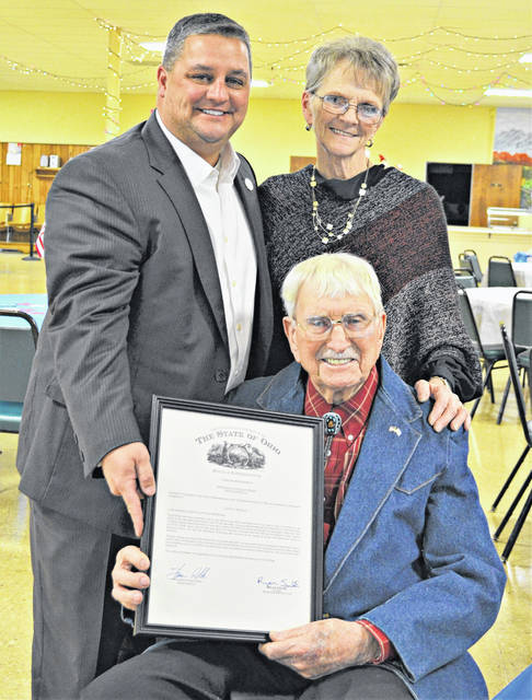 "State Rep. Shane Wilkin made a surprise visit to the Highland County Senior Citizens Center Saturday for local veteran Major Floyd ""Mac"" McCray's 95th birthday open house. Wilkin presented McCray and his wife Judy with an official proclaimation from the Ohio State House recognizing McCray for his years of service in World War II, Korea and the Cold War, and his service to his communty as well which included helping with construction of the Highland County Veterans Memorial at the rear of court house square. Pictured are Wilkin, McCray and his wife Judy, standing behind him."
