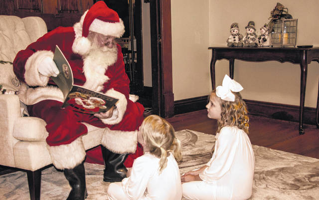"Santa Claus took some time out of his busy schedule in recent days to read ""'Twas the Night Before Christmas"" to Addie and Aubree Hoop at Hillsboro House, a local lodging place. Claus rested at Hillsboro House the night before visiting children of all ages at the Highland County Senior Citizens Center's Breakfast with Santa fundraising event recently. Mechell Frost, executive director of the senior center, thanked Hillsboro House for putting up the jolly old elf, adding, ""Santa loved his warm and comfortable stay."""