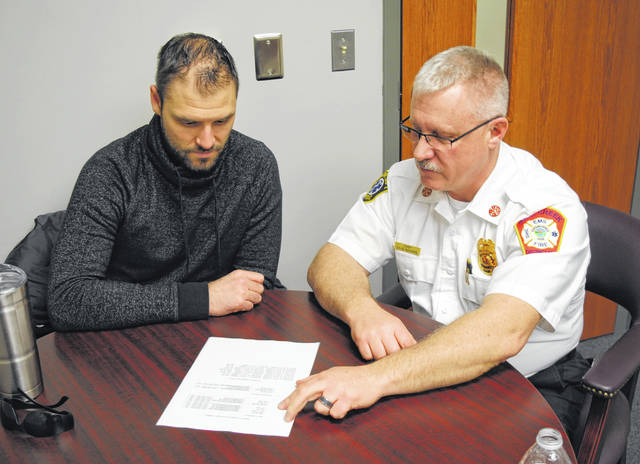 Good News Gathering Associate Pastor J.D. Lyle, left, reviews a chaplain roster with Paint Creek Joint EMS/Fire District Chief Dave Manning. Not shown is Capt. Matt Miller, who coordinated with local pastors to provide a chaplain service for Paint Creek.