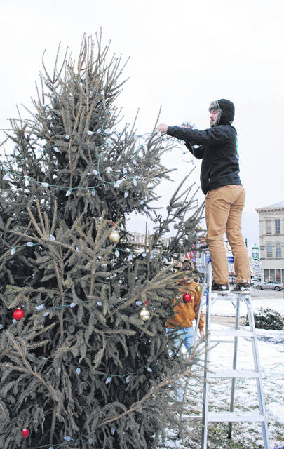 Cole Newsome of Hillsboro High School wraps lights around the Christmas tree on the Highland County Courthouse lawn Wednesday afternoon. Newsome and other members of the Hillsboro High School Student Council braved cold and snow flurries to decorate the tree, which was placed in front of the judicial building earlier this week with help from Lerch's Barnlot LTD staff. Before and after this Saturday's Hillsboro Lighted Christmas Parade, which begins at 6 p.m., student council members will be selling hot chocolate for donations. All money raised will be used for the school's Adopt-A-Family Christmas program next year.