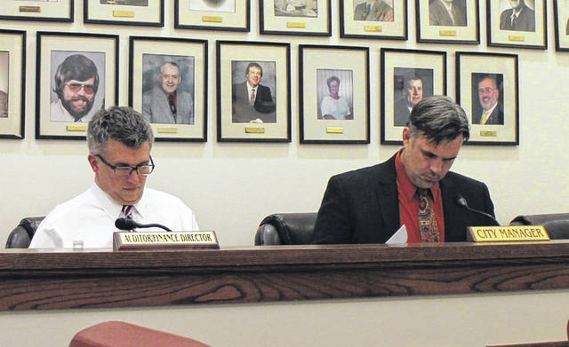 Greenfield Law Director Brian Zets, left, and City Manager Todd Wilkin, right, review paperwork during Tuesday's Greenfield Village Council meeting.