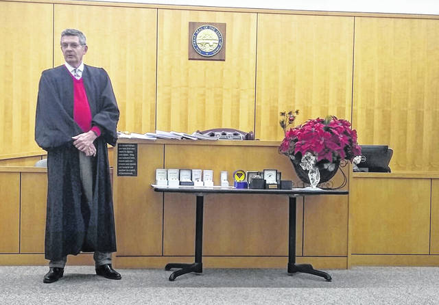 Judge David McKenna of Hillsboro Municipal Court speaks to graduates of the court's Vivitrol program on Monday. The judge is shown next to a table of wristwatches given to participants as parting gifts.
