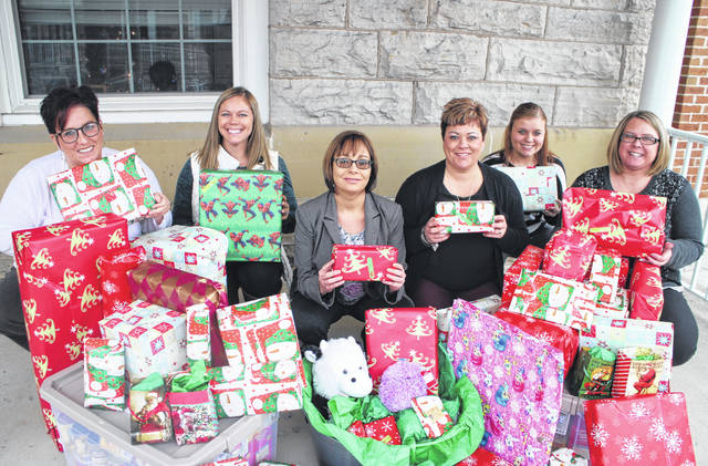 Highland County Prosecutor's Office staff are shown holding Christmas gifts Thursday afternoon before delivering them to local families in need. The yearly tradition, which began in 2011, involves the prosecutor's office identifying families in poverty and giving them personalized Christmas presents and food for the holiday, according to Prosecuting Attorney Anneka Collins. Shown from left are Highland County Victim-Witness Office Director Niki Glispie, Assistant Prosecuting Attorney Molly Bolek, Collins, Tara Smith-Decker, Rylee Ruble and Kathryn Allen.