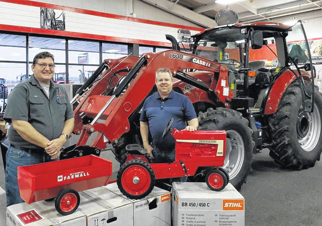 John Frazier, left, of Bane-Welker Equipment, and Ag Is Everyone's Business committee member Brad Elmore are pictured with the Farmall pedal tractor and grain cart.