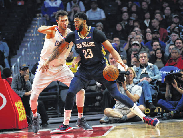 FILE- In this Jan. 14, 2019, file photo New Orleans Pelicans' Anthony Davis, right, dribbles against Los Angeles Clippers' Danilo Gallinari during the first half of an NBA basketball game in Los Angeles. Davis' agent says the five-time All-Star has told the New Orleans Pelicans that he wants to be traded to a contending team. Agent Rich Paul confirmed the request to The Associated Press early Monday, Jan. 28.